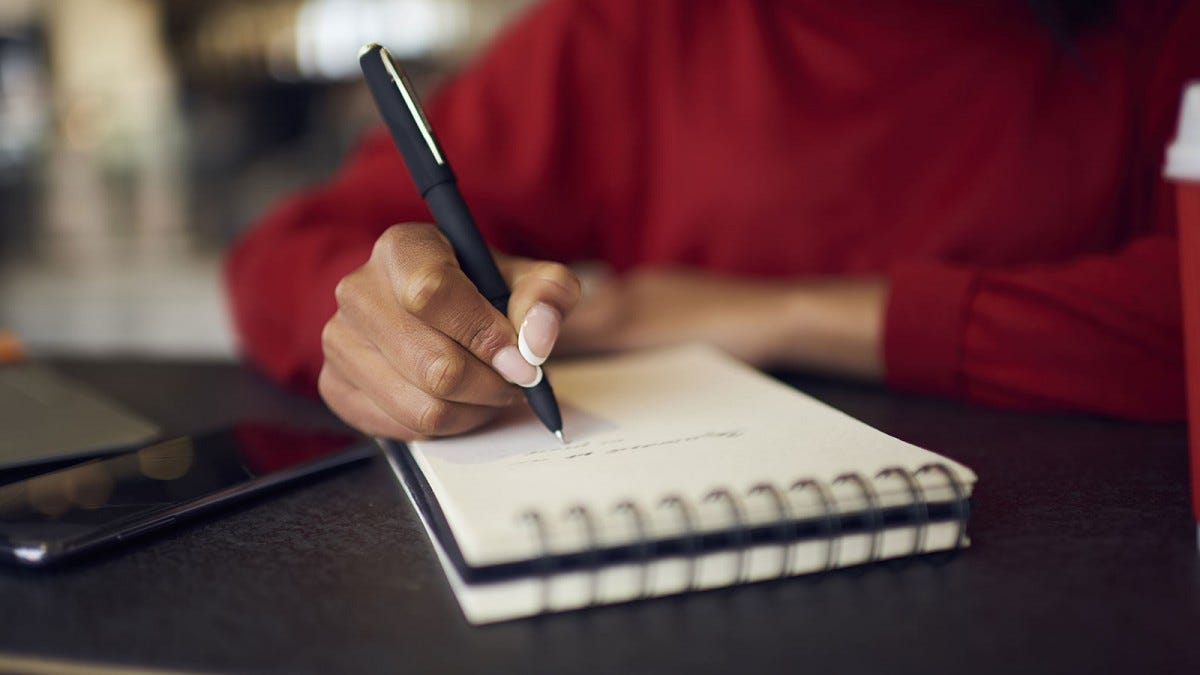 A woman's hand writing in a notebook.