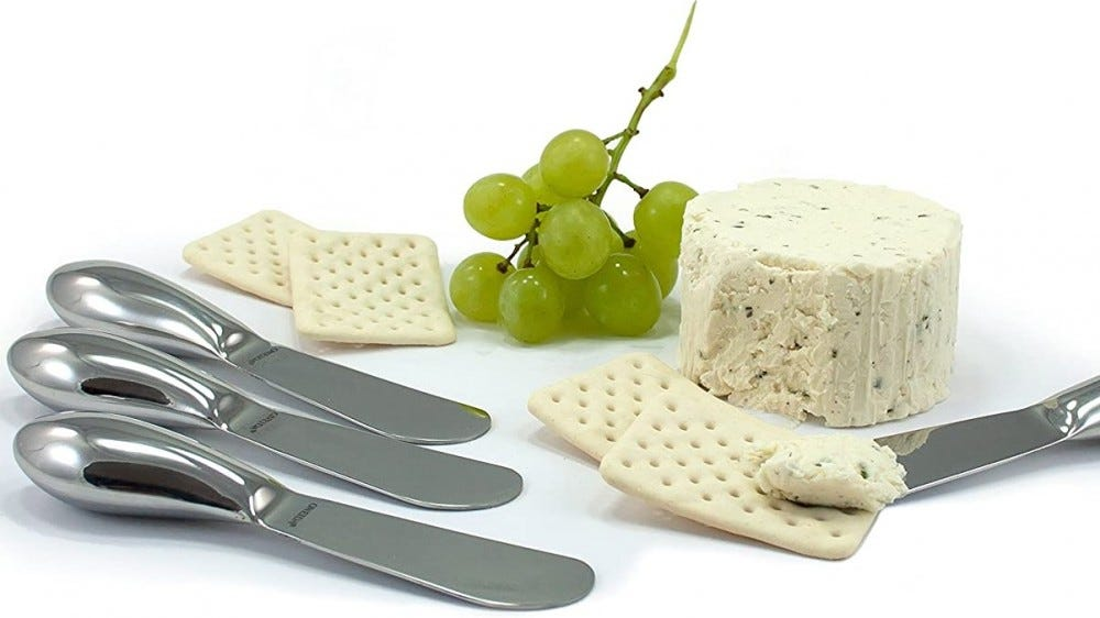 Cheese knives on a table with soft cheese and crackers.