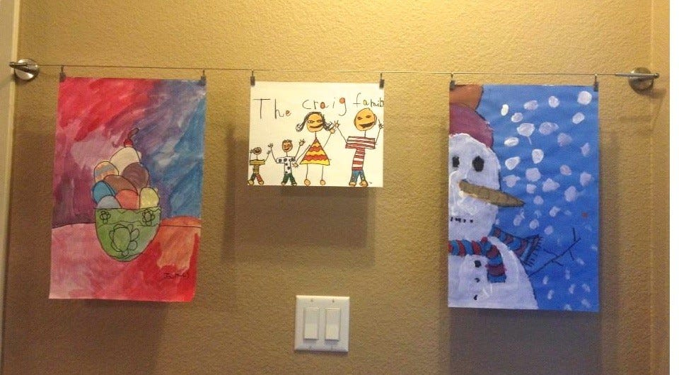 An IKEA wire art hanging system displaying three paintings by a child.