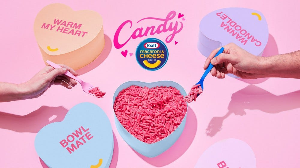A heart shaped bowl full of pink Kraft macaroni and cheese and surrounded by oversized candy hearts.