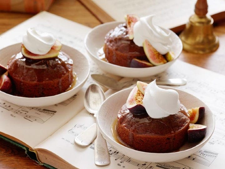 Three figgy puddings in three separate bowls topped with fresh fig and whipped cream.