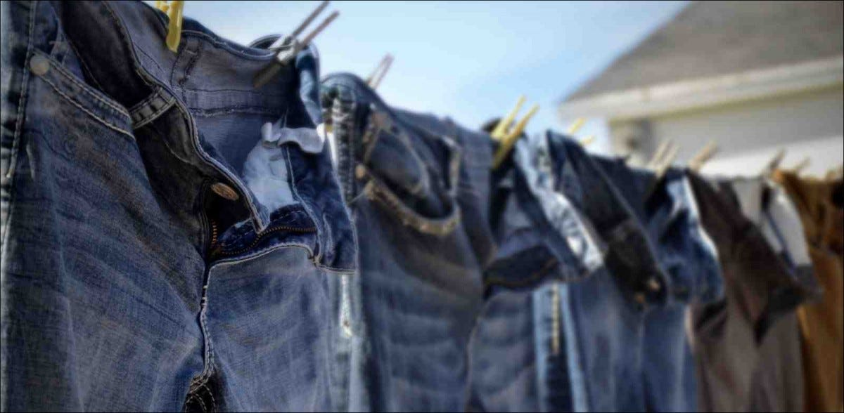 A side view image of freshly washed denim jeans hanging on a clothesline