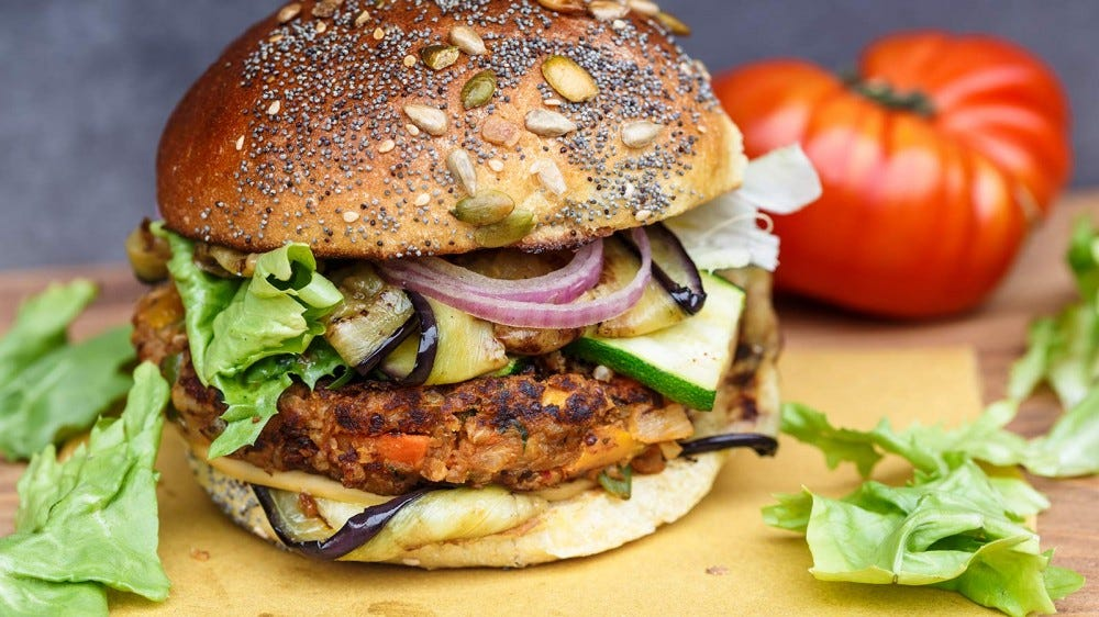 A veggie burger piled high with toppings, resting on a cutting board.
