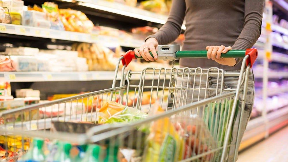 Woman pushing a shopping cart through a grocery store.