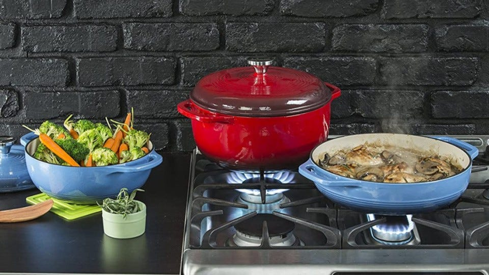 A shallow blue cast iron dish cooking chicken and mushrooms on a stove top, with a red, deep cast iron dutch oven in the background and some vegetables set to the side.