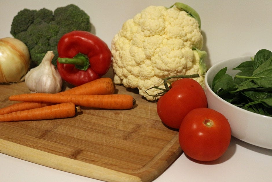Multiple vegetables including carrots, broccoli cauliflower, tomatoes and spinach.