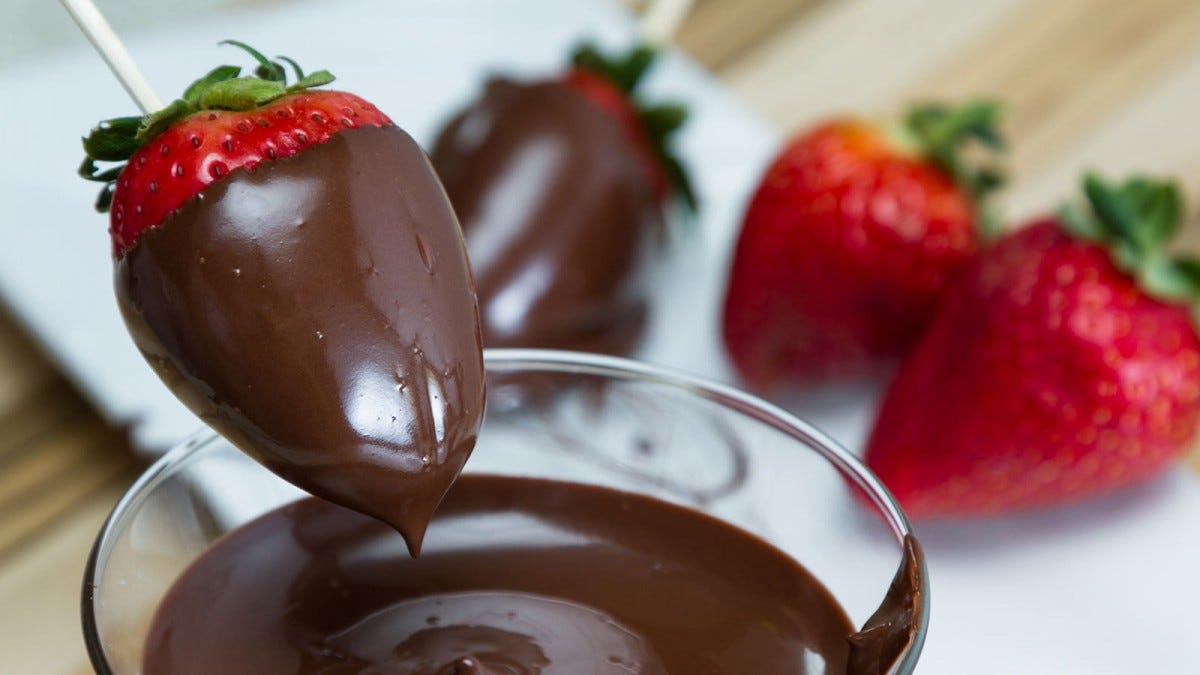 A chocolate-covered strawberry on a stick being held over a glass full of melted chocolate.