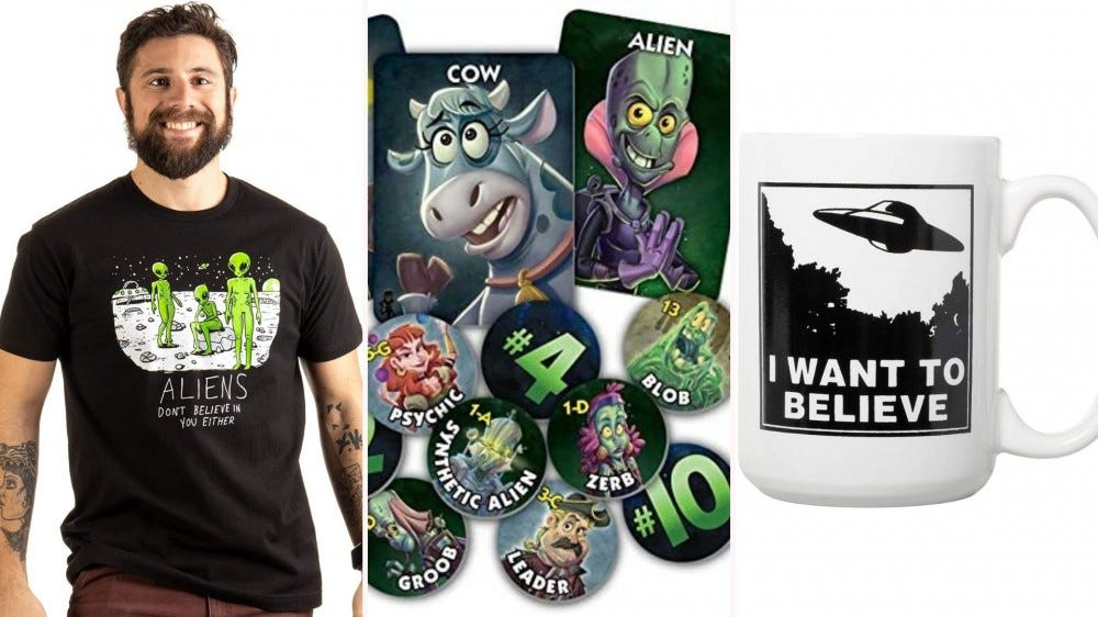 """A man wearing an alien T-shirt, game pieces from the """"One Night Ultimate Alien"""" game, and an """"I Want to Believe"""" mug."""