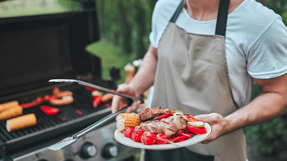 A man standing next to a grill, holding tongs and plate full of grilled foods.