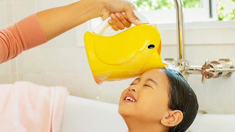 A woman using the bath rinser on a child in the tub.