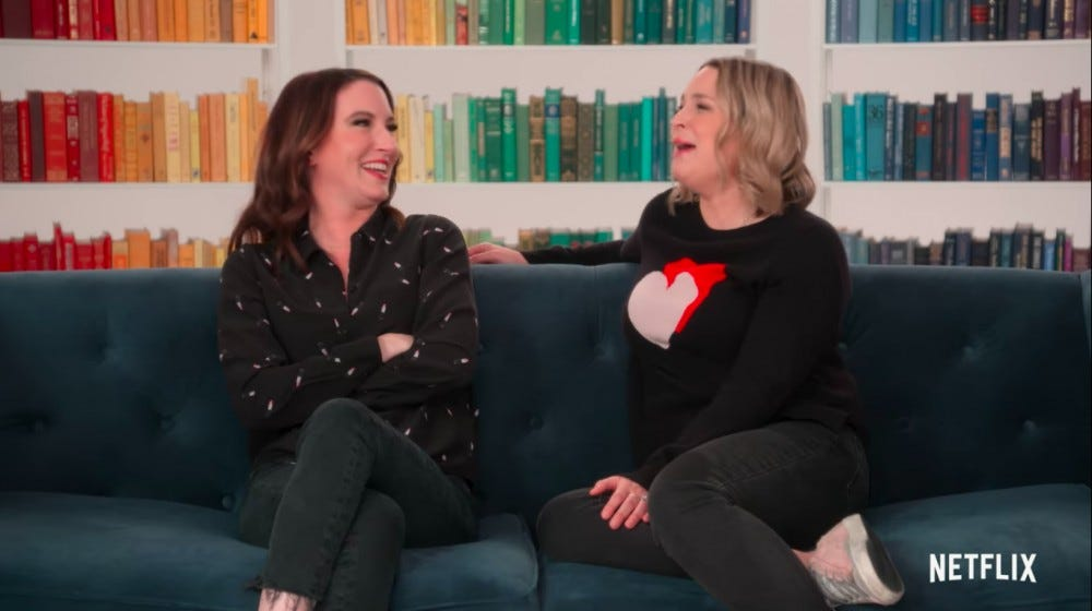 Two women sit on a blue couch with a bookshelf arranged by color behind them.