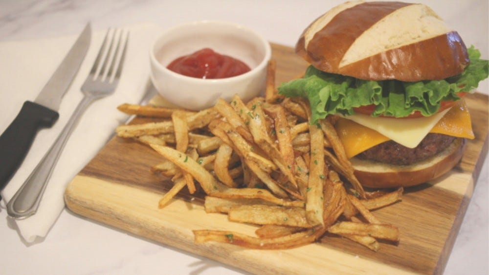 A burger on a bun sitting on a cutting board with a side fries and a dish of ketchup.