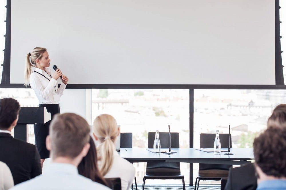 Business woman speaking into microphone while giving a presentation.