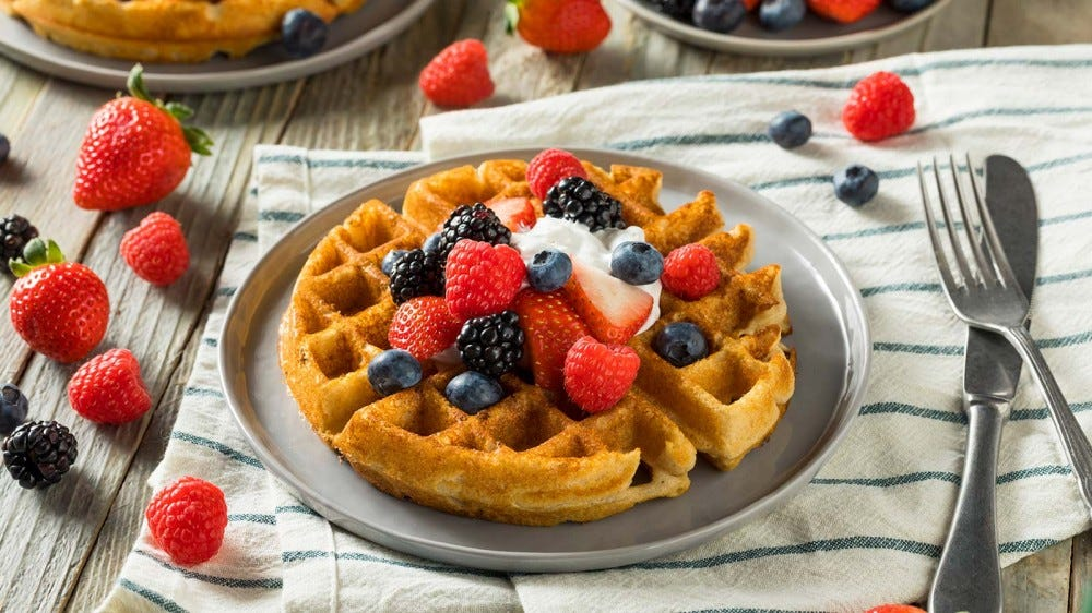 A freshly made waffle on a gray stoneware plate, topped with whip cream and fresh fruit.
