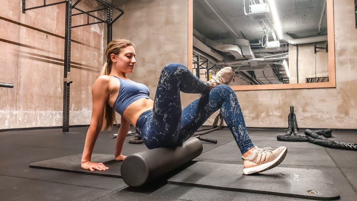 A woman in a gym sitting on a foam roller with one leg crossed over the other.