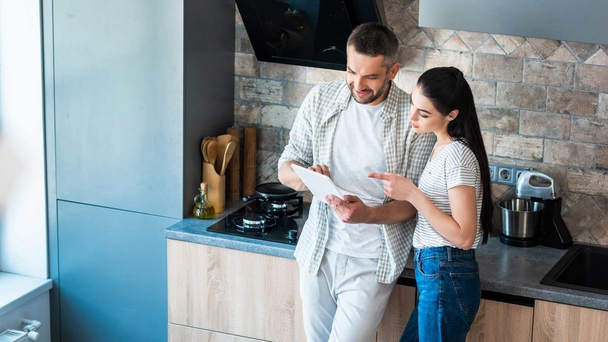 A man and woman looking at a piece of paper in a kitchen.