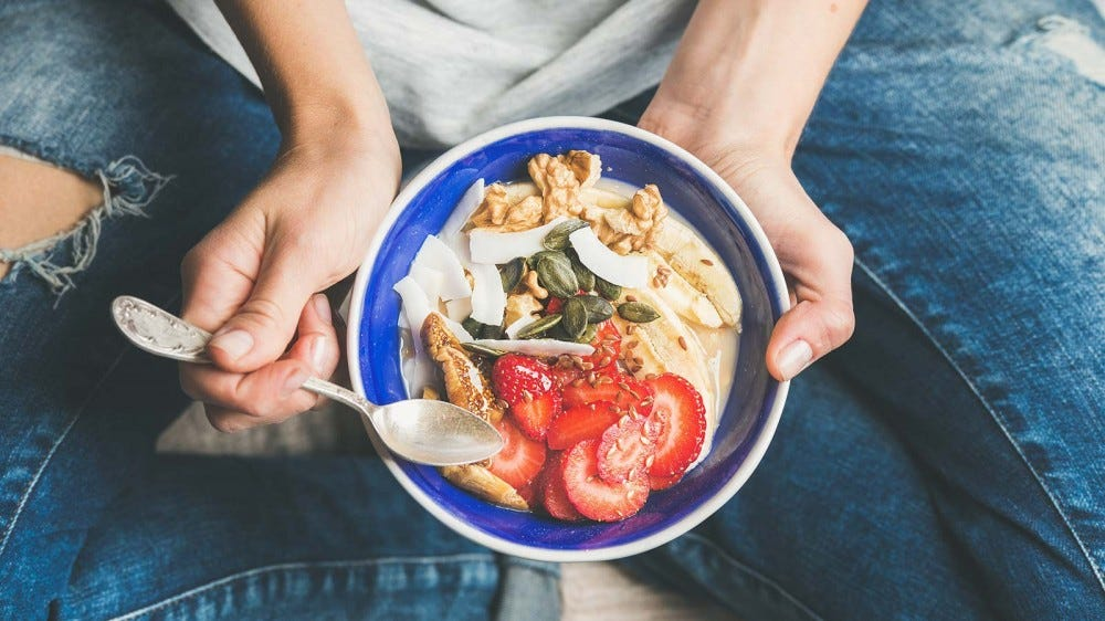 Someone holding a yogurt bowl loaded with fruit, nuts, and other healthy toppings.