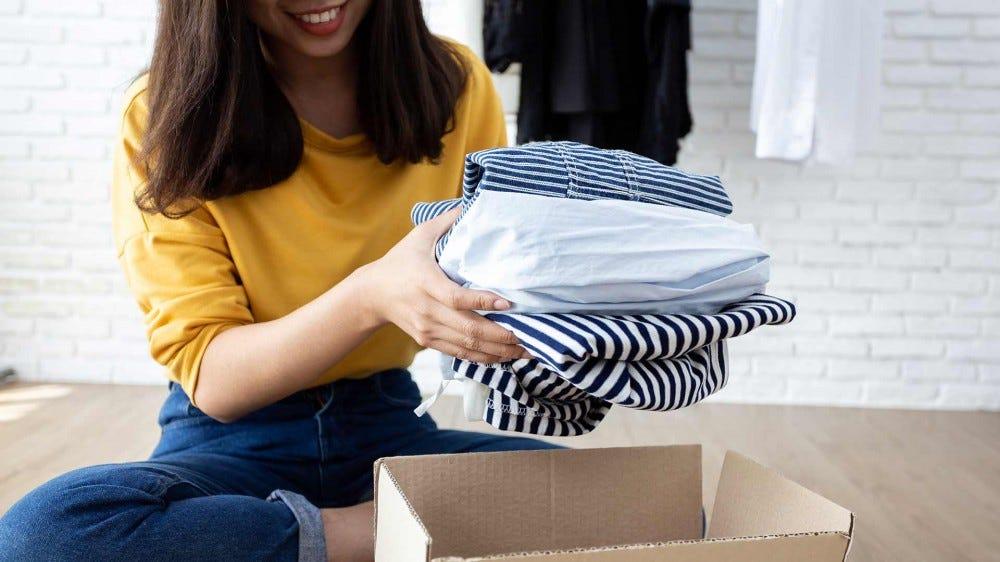 Egy nő takarítja ki a szekrényét, és összecsomagol ruhákat adományként.