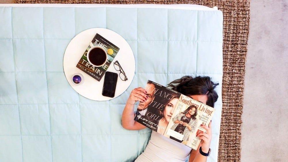 A woman lying on a Slumber Cloud Nacreous Mattress Pad, reading a magazine.