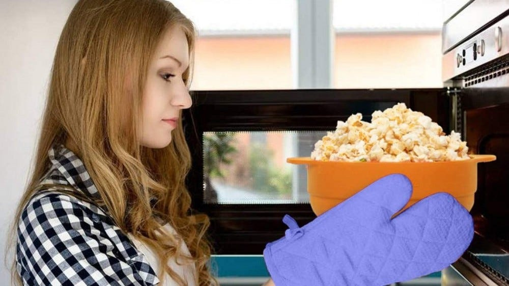 Woman removing popped popcorn from the microwave.
