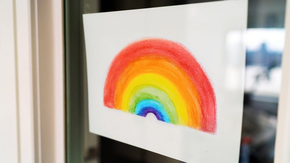 A rainbow drawing hanging in a window.