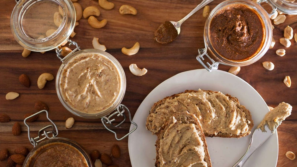 Different kinds of butters in jars on a table, next to a plate with bread covered in almond butter.