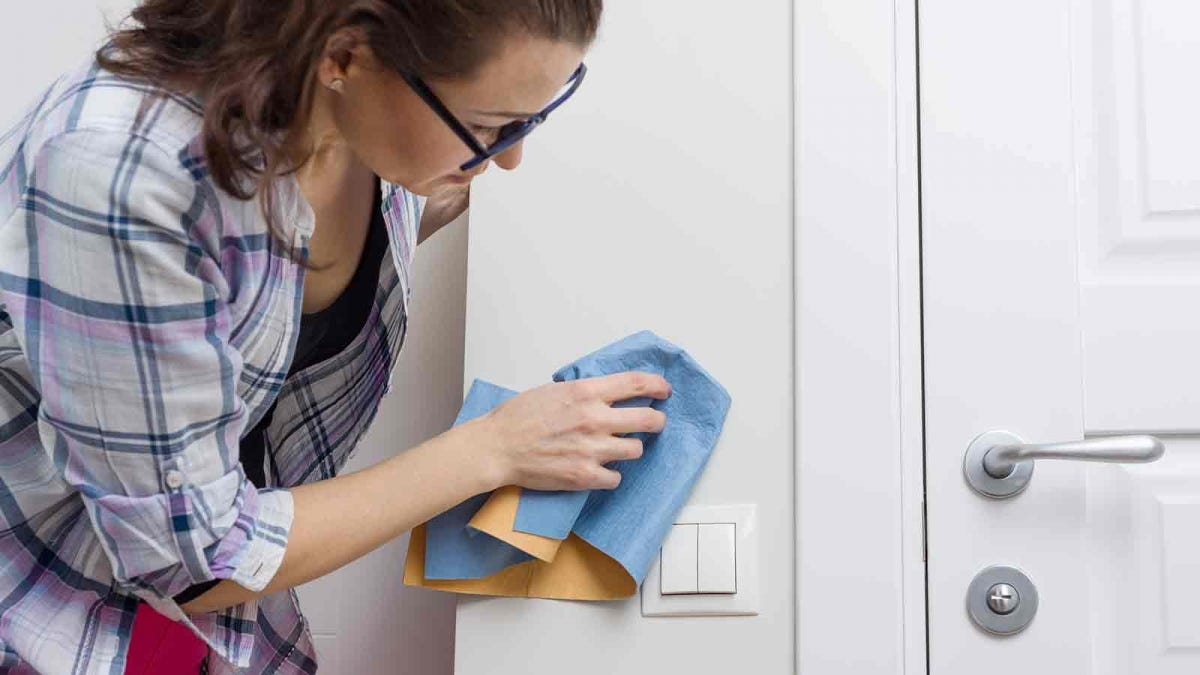 Woman cleaning walls with a microfiber rag