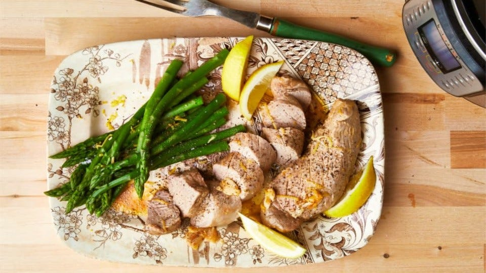Pork tenderloin and asparagus, on a lovely decorated plate, served with fresh lemon wedges, along side an instant pot.
