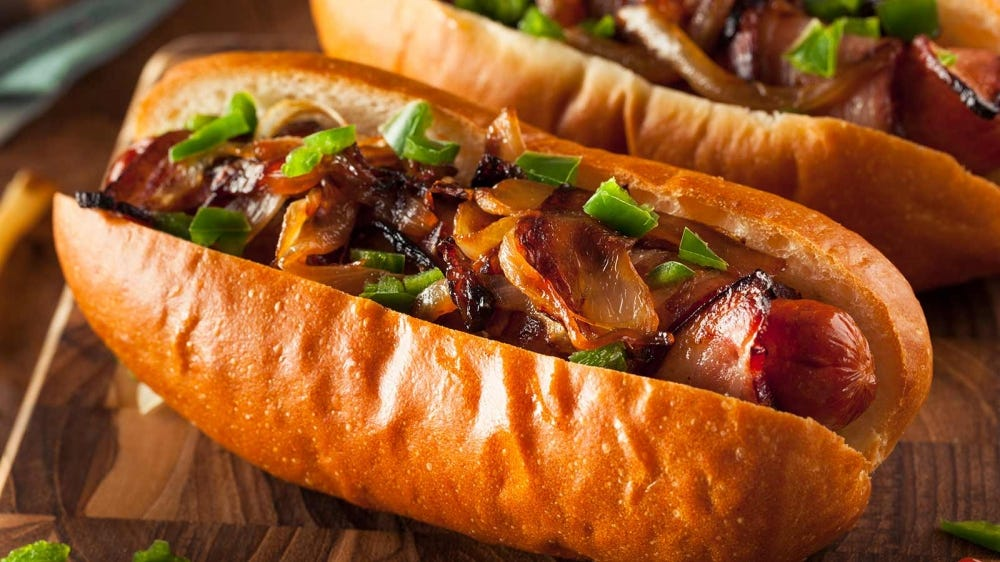 Hotdogs garnished with sauted peppers and onions.