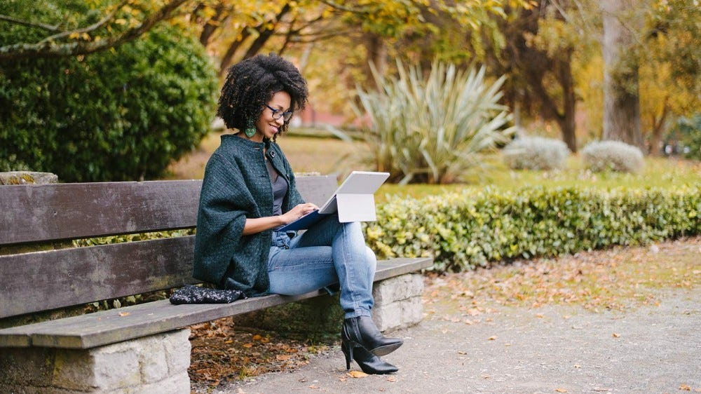 A woman sitting on a bench at a park and working on a tablet computer.