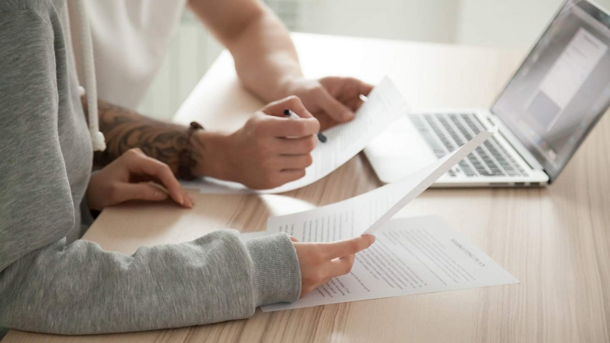 A man and woman's hands holding documents in front of a laptop.