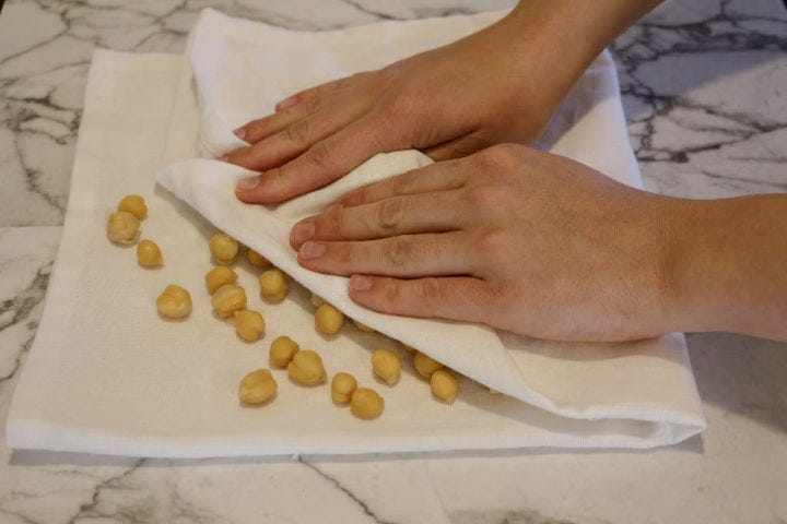 Hands pressing half a towel over some chickpeas resting on the other half.