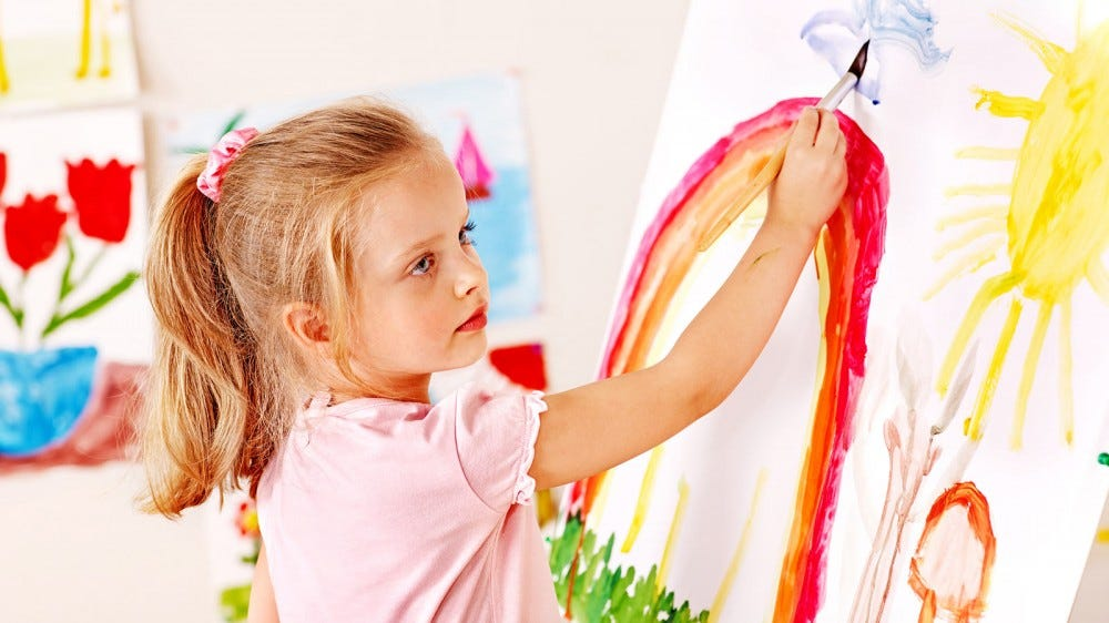 A young girl painting on a large canvas.