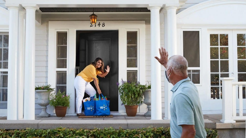A woman waves from her porch to a walmart delivery service driver as she picks up groceries.