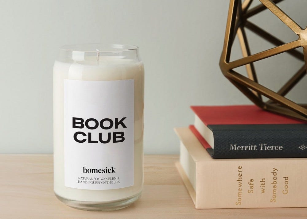 An unlit Homesick Book Club candle next to a stack of books on table.