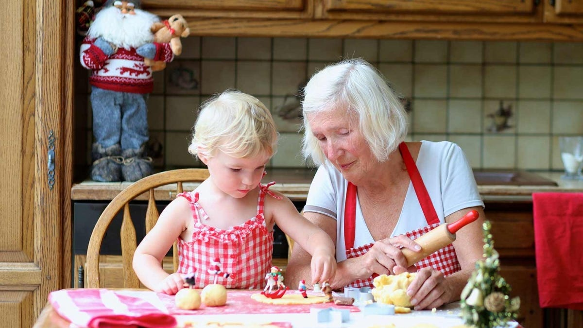 A doting grandmother making cookies with her granddaughter.