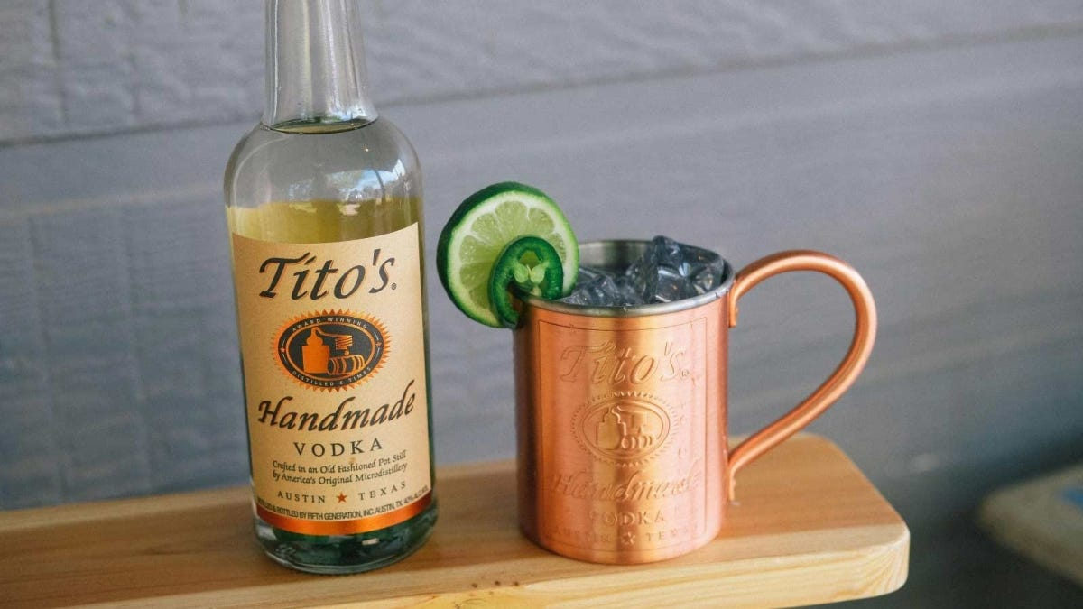 A bottle of Tito's Vodka next to a copper Moscow Mule mug.