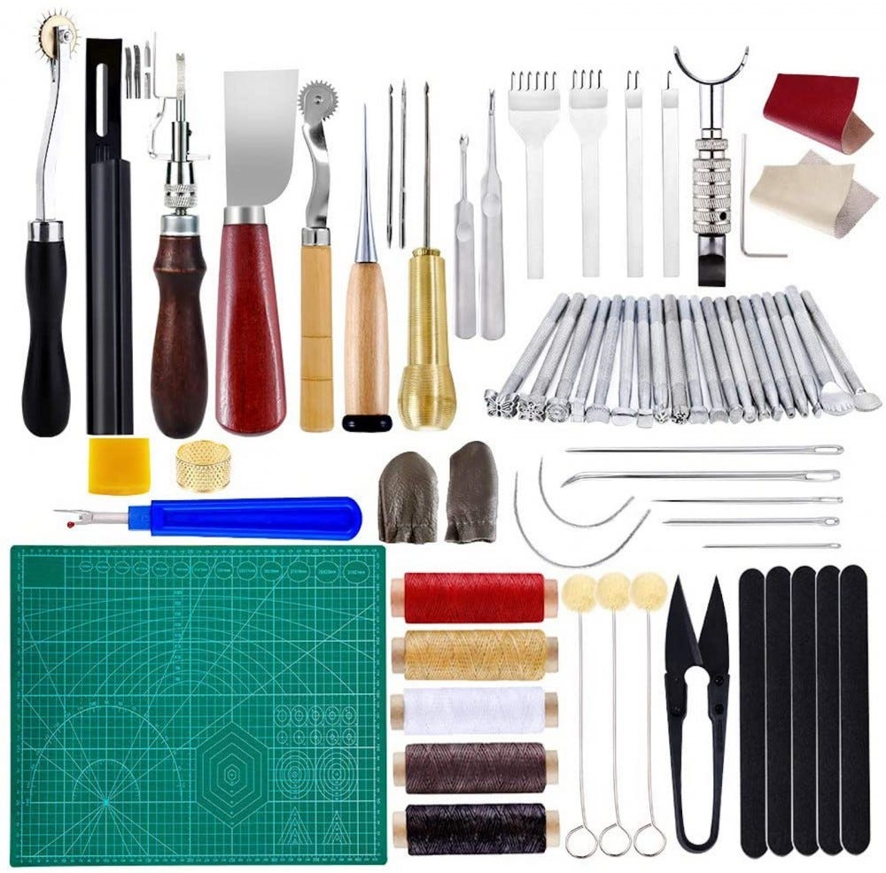 A variety of wood and metal tools for leather working laid out side by side