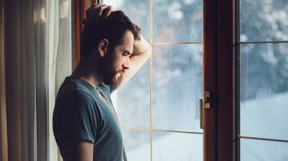 A sad-looking man standing at a window overlooking a snowy landscape.
