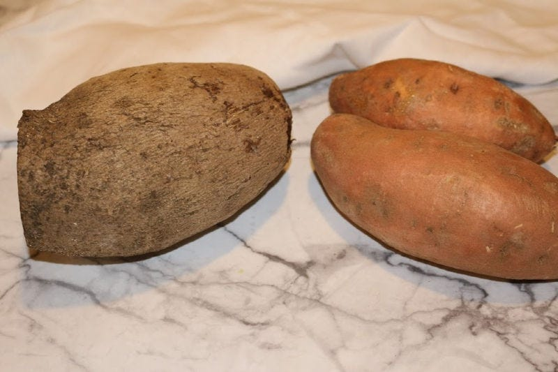 One yellow Ñame yam on the left, and two sweet potatoes on the right.