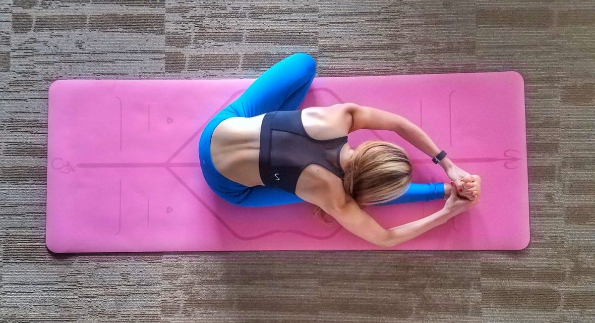 Woman doing a seated one-legged forward fold on a pink yoga mat