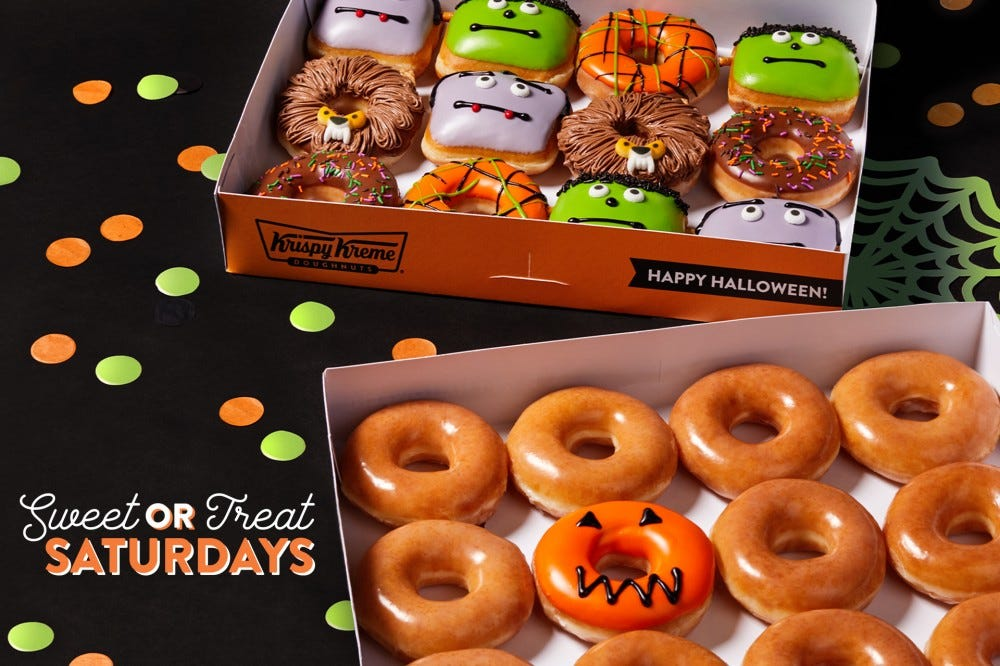 Two dozen doughnuts — one with various monster designs the other a collection of plain glazed — sit in Krispy Kreme containers.