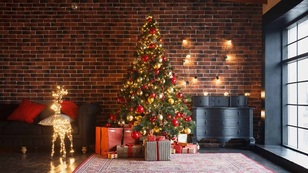 A beautiful Christmas tree next to a sunny window in a brick-walled loft.