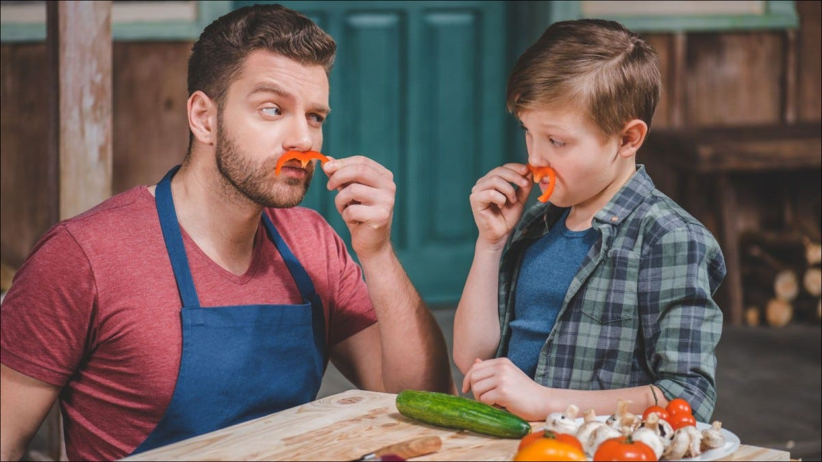 Father and son chopping vegetables and making bell pepper mustaches