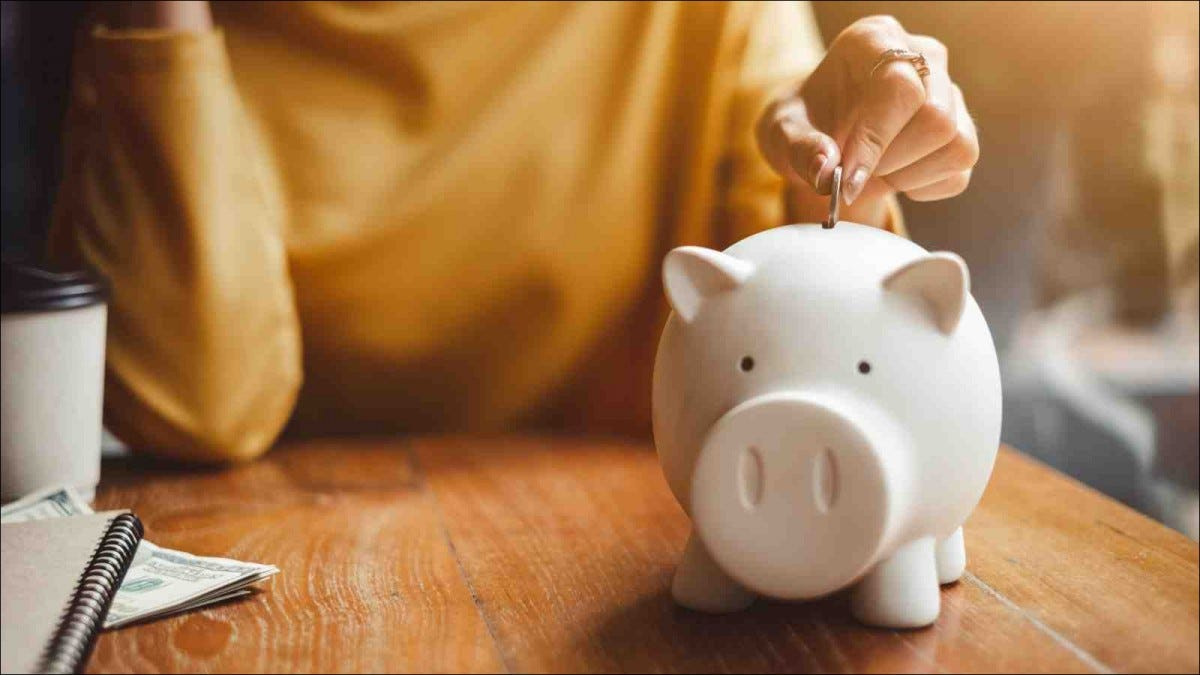 closeup of woman's hand putting coin in piggy bank