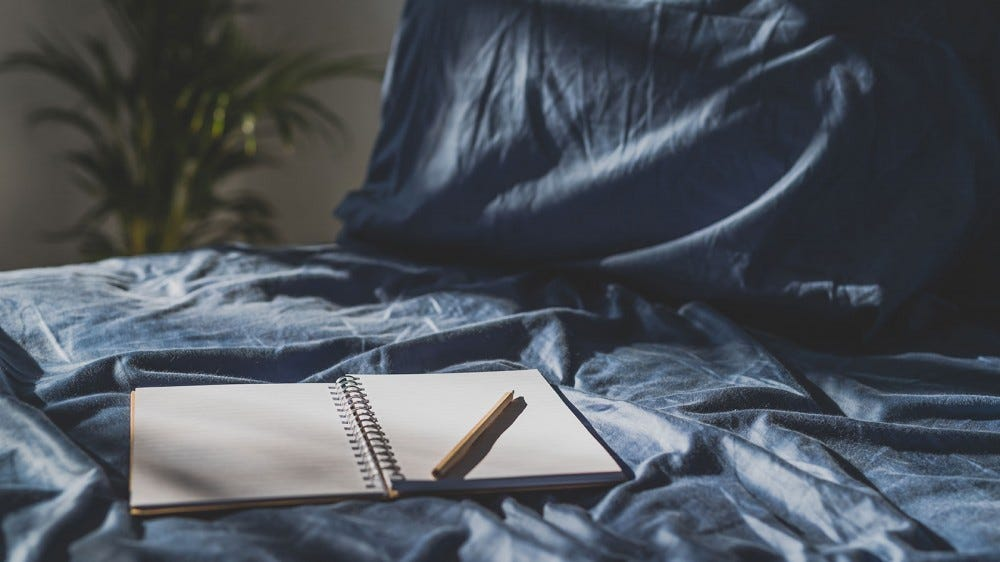 A journal laying on blue sheets.