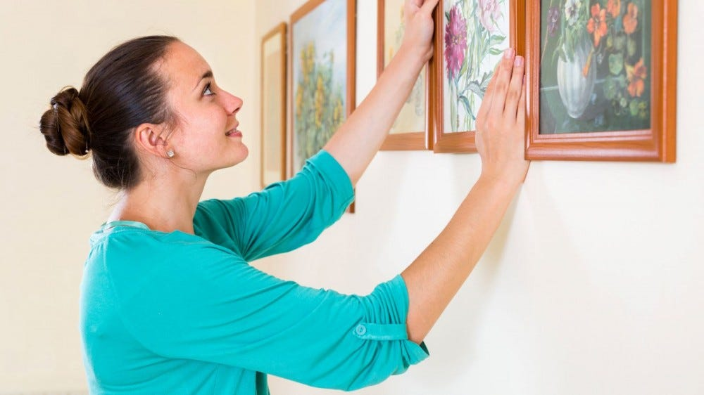 A woman hanging a painting on a wall.