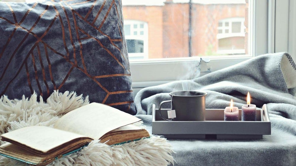 A window seat with a pillow, fuzzy blankets, a book, and a tray with two candles and a mug.