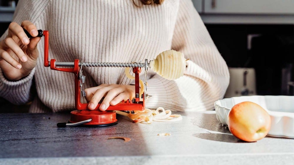 A woman using a table-top apple peeler to core and peel apples for a pie.