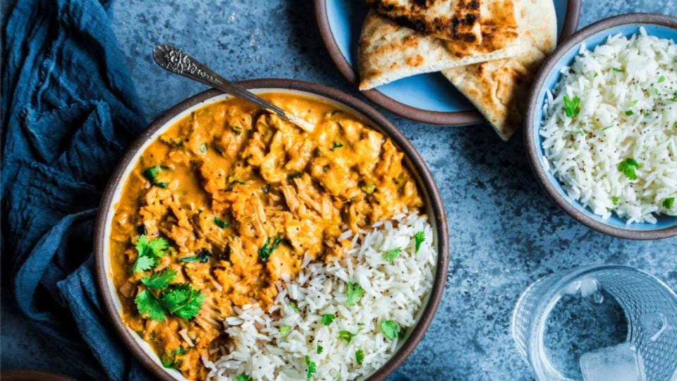 A bowl of spicy jackfruit curry served with basmati rice and a side of warm pita bread.
